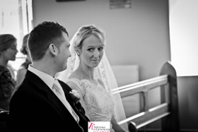 The look of love - bride and groom seated near the altar